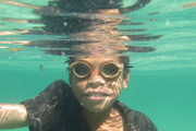 Young child wearing googles under water