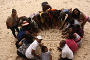Group of kids writing on the sand: My World, My SIDS, YES
