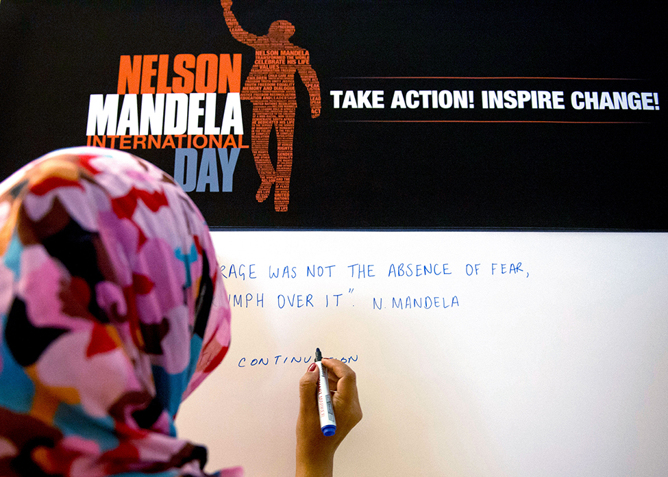 A participant writing a message on a board in commemoration of Nelson Mandela International Day.