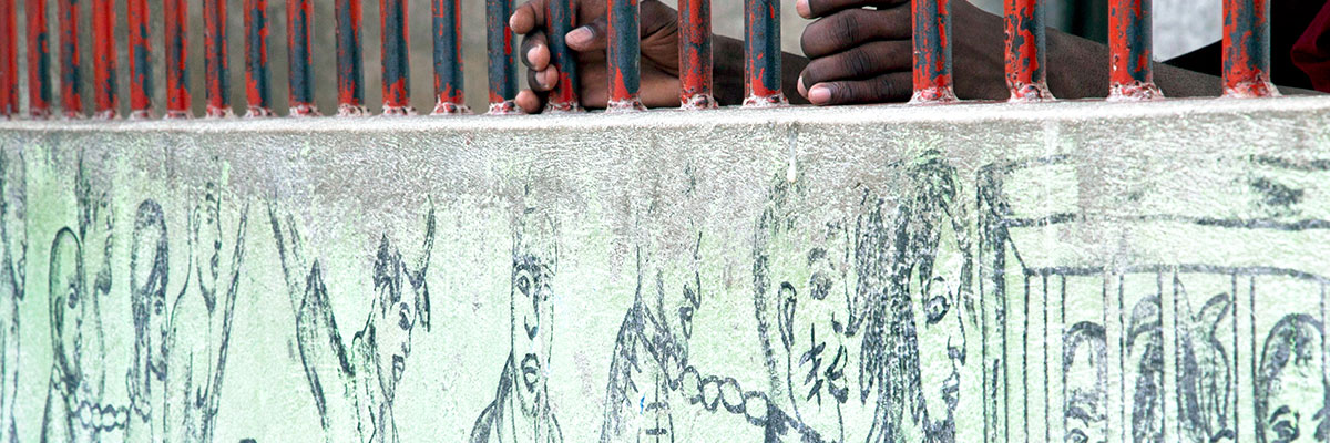 An inmate grasps the bars of an outside wall at the Penitentiary on which a mural of prisoners has been drawn. Port-au-Prince, Haiti. UN Photo/Victoria Hazou