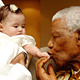 Mr. Mandela kissing the hand of a baby.