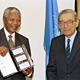 President Nelson R. Mandela (left) of South Africa displays a book that he received from Secretary-General Boutros Boutros-Ghali. The book is about the United Nations and its efforts against apartheid.
