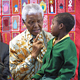Mr. Mandela with a child on his lap, talking to her. Taken during meetings about HIV/AIDS in November 2004.