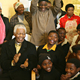 Mr. Mandela, surrounded by children, clapping his hands & 90th birthday cake on the table