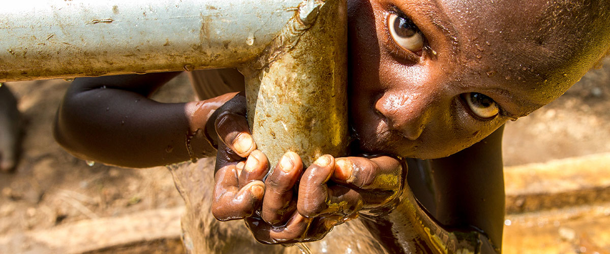 Marakera, an Ethiopian 5-year-old boy, drinks clean piped water.