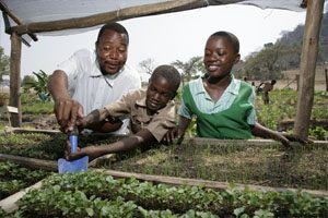 Here, students and the school master plant crops for the garden at Nhema Primary School.