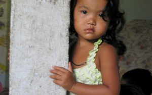 A young child looks at a camera while leaning against a wooden pole. She is wearing a black necklace and a light green singlet.