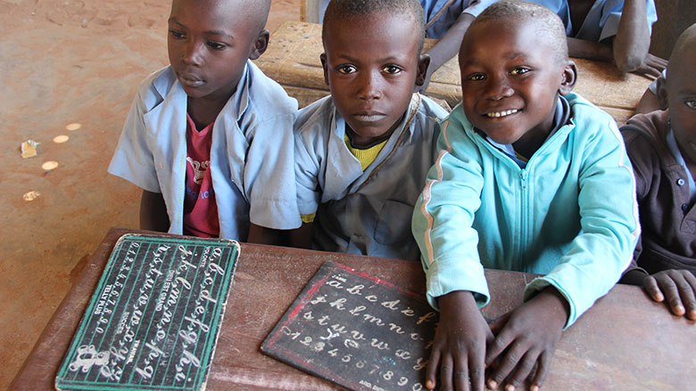 Three young children sit at a wooden desk. They have small chalkboards on their desk with white writing on it. Underneath them is a dirt floor.