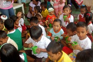 Young children sit on the floor of a classroom eating a meal out of small green cups with a spoon.