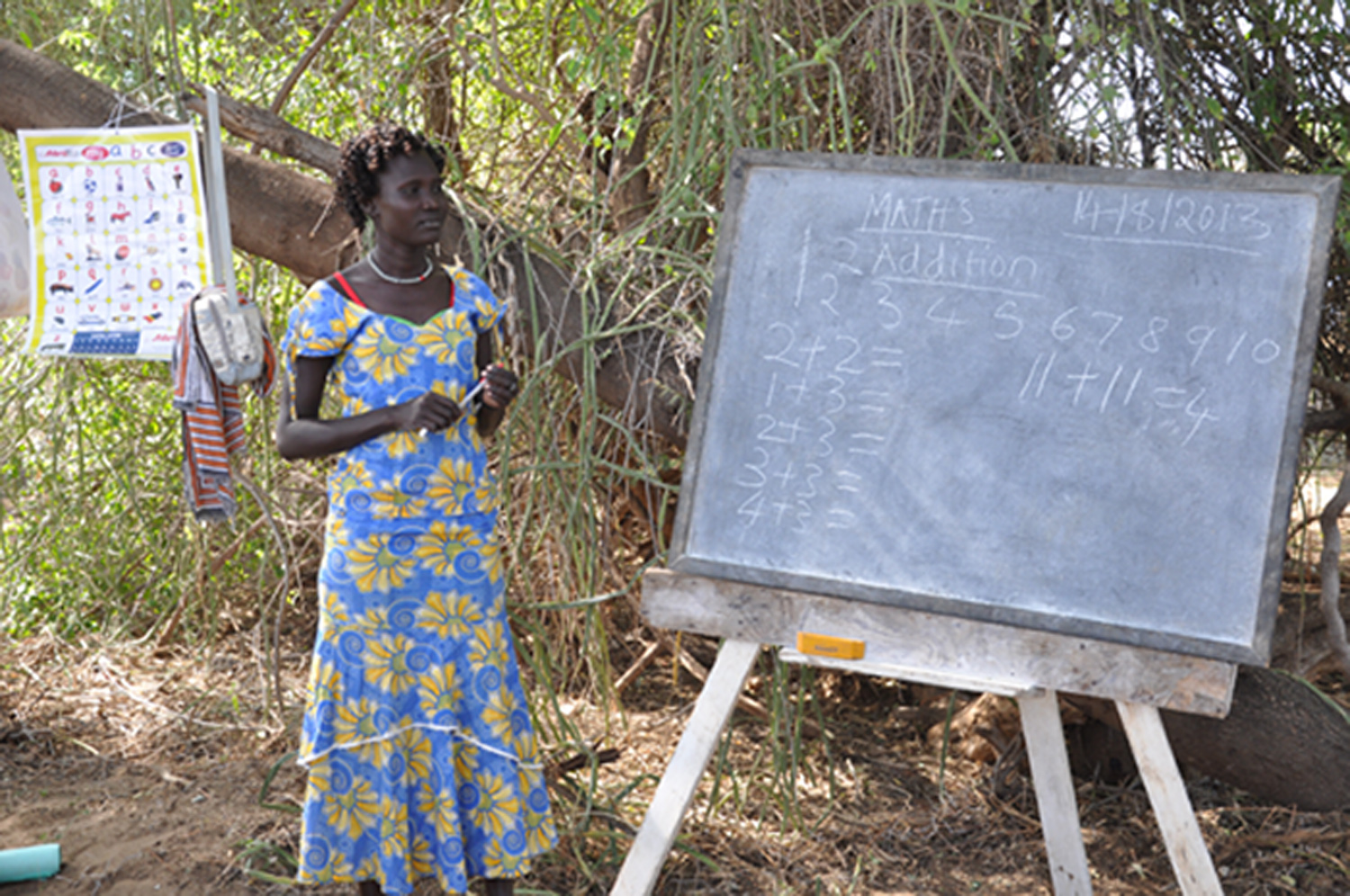 A woman is standing next to a blackboard, on which math problems have been written. A colorful poster with the alphabet is hanging behind her.