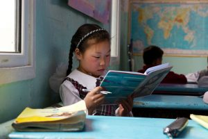 A young Mongolian girl sits at her blue desk reading a book which she is holding in her hands. There are several students sitting behind her in the classroom and there is a map hanging on the wall.