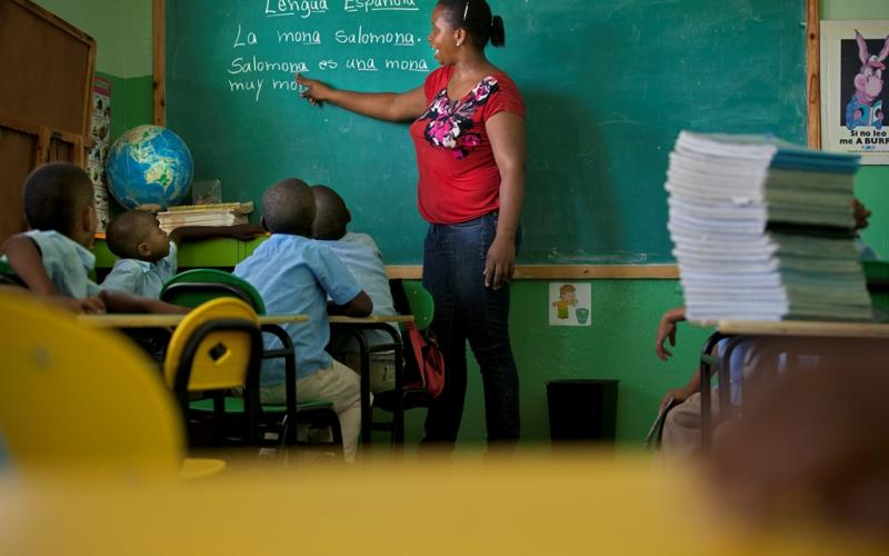 A teacher stands in front of a green chalkboard and points to text that has been written on the chalkboard. Four young students on her right are sitting at their desks and are reading from the chalkboard.