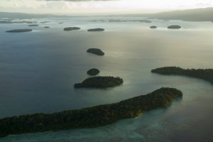 An aerial shot of a lagoon in the Solomon Islands at sunrise. There are several islands scattered throughout the lagoon.