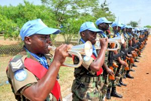 Peacekeepers are lined up with blue military caps. They are simultaneously blowing into trumpets.