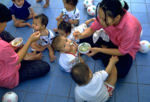 A woman sits on a blue tiled floor and spoon feeds a child from a bowl. There are several other children sitting on the floor, in addition to small soccer balls.