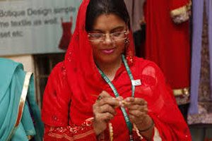 A woman dressed in red clothing is wearing glasses and is focused on a sewing task.