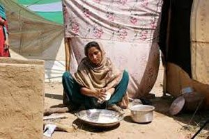 A woman sits on a dirt ground in front of a basic silver cooking stove. There is a sheet hanging behind her, and a tent in the background.
