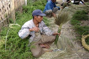 A man sits on the ground with open shoes and is weaving plants using bamboo and string. There are several other men behind him who are also weaving.
