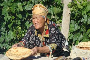 An old woman leans over a wooden table holding a round piece of baked bread.