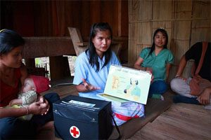 A young woman sits in a wooden house surrounded by three other women. One of the women is carrying a child. There is a medical kit next to the woman speaking, and she is holding a diagram of a mother and her child.