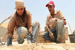 One young man and one older man holding construction tools on a worksite, placing bricks in position to assist with the construction of a new building.