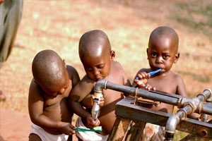 Three young children are shown at a water faucet and are brushing their teeth.
