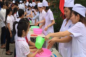Girls dressed in white clothing with white hats stand at desks and wash the hands of smaller girls using bright green and pink plastic bowls and cups.