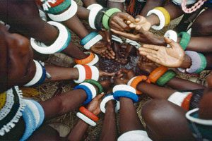 The picture shows colorfully banded arms of young men of the Ndebele tribe of South Africa engaging in an initiation ceremony.