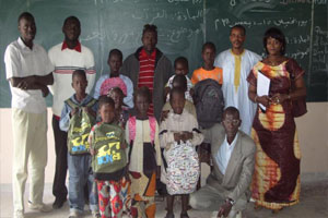 A group of people, including several children, are standing in front of a blackboard.