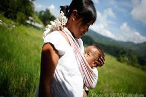 A woman stands in a mountainous field. She is carrying a baby in a sling which is tied around her neck and shoulders.