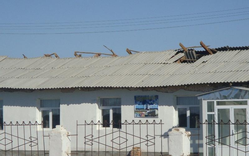 The photo pictures a medical centre with a damaged aluminium roof. There are holes in the roof and damaged boarding.