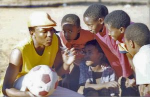 A young man holding a soccer ball in one of his hands gathers a small group of boys, who are attentively listening to him.