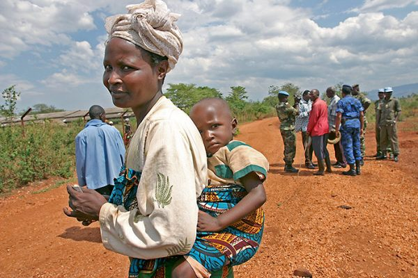 A mother has her child tied to her back while smiling at the camera. Behind her, a group of men have gathered in a small circle.