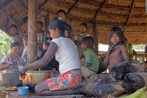 A woman cooks in a pot surrounded by young children who are watching her cook. They are all sitting in a hut.