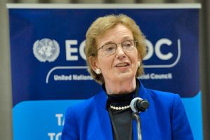 Mary Robinson is wearing a black shirt and blue blazer and is speaking into a microphone. Behind her is a sign stating 'ECOSOC.'