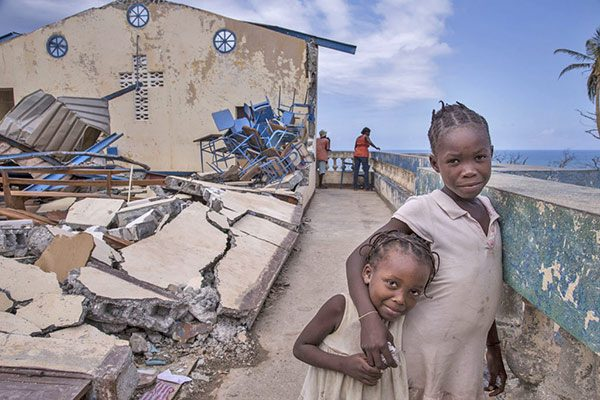 Two young girls stand on the balcony of a destroyed building. There is an ocean in the backdrop. They are surrounded by rubble and torn aluminium.