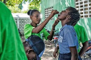 A young Haitian male opens his mouth to receive drops from a member of a local medical team.