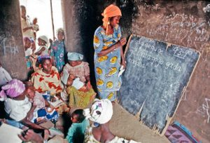 Women are pictured attending an adult literacy class in a village near Bauchi. A woman is writing on a chalkboard which is leaning against a wall.