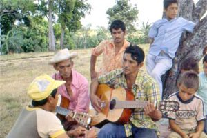 A small group of refugees rest under a tree in a field in Panama. Two of the individuals are playing guitars.