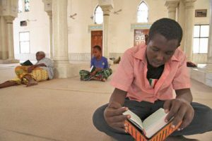 A boy reads from his Koran at a mosque in Mogadishu, Somalia, during the holy month of Ramadan. There are two other boys sitting behind him.