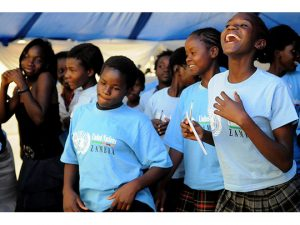 "A group of smiling children are wearing blue shirts stating: ""United Nations Zambia"" shirt."