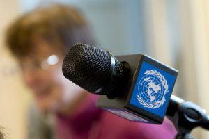 The photo shows a microphone with a UN logo attached to it. There is a woman in the background who is out of focus.