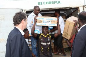 A man removes boxes from a van. He is carrying the box on his head, and on the box are UNICEF stickers. There are several men standing behind him who are also unloading boxes from the van.