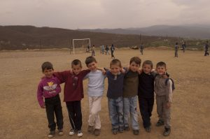 Seven young students stand at the camera smiling, with their arms around each other's shoulders. They are standing in a dirt soccer field, and there are young boys playing behind them near a soccer goal. There are mountains in the backdrop.