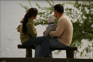 A woman and man sit on a park bench with their legs crossed together. The man has a child on his lap who is wearing a beanie. They are looking out into the distance and there is a tree in the background.