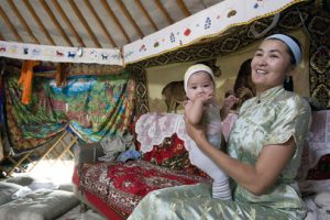 A woman wearing a silk traditional dress holds an infant. They are sitting on a lounge covered in a colourful rug.