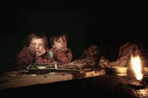 Two children sit in a dark setting with their heads in their hands. The area is dirty and there is a fire flickering on the right hand side of the photo.
