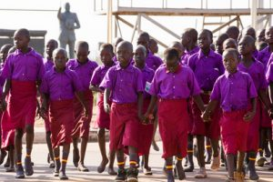 The picture shows a large group of young children dressed in purple shirts and red trousers.