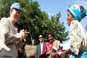 Ban Ki Moon stands next to a group of people watching a woman on the right. She is smiling and is holding a cob of corn. There is a bale of hay behind them and a large tree.