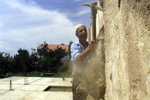 An elderly man chips away at a wall with a hammer like tool. He is standing on a cement floor and is surrounded trees.
